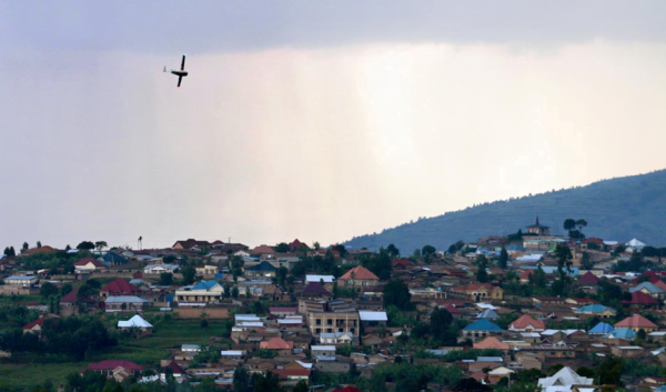 An aeroplane flying through the sky over a village.